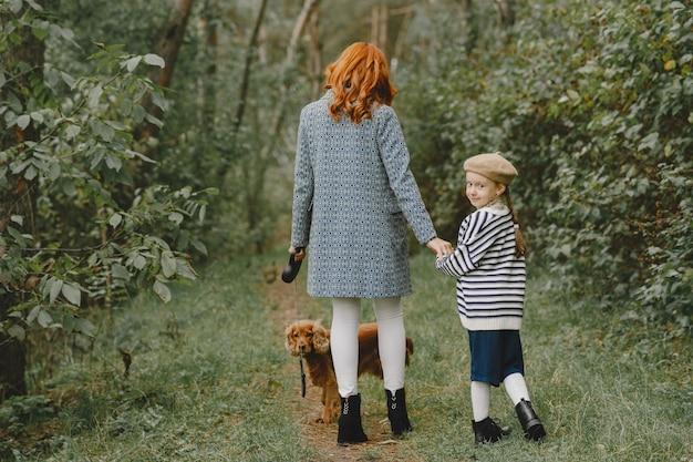犬と遊ぶ母と娘。秋の公園の家族。ペット、家畜、ライフスタイルのコンセプト。秋の時間。 無料写真
