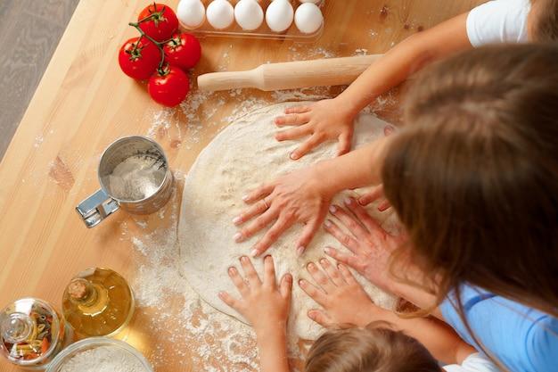 Мать и ее дети замешивают тесто на кухонном столе Premium Фотографии
