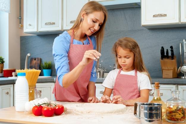 Мать и ее маленькая дочь готовят тесто на кухне Premium Фотографии