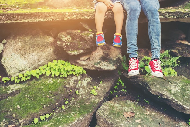 Mother and her little son feets sitting at the cliffside. Free Photo