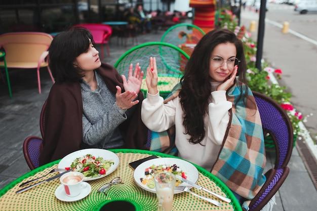 母と彼女の若い娘がカフェで一緒に座る Premium写真
