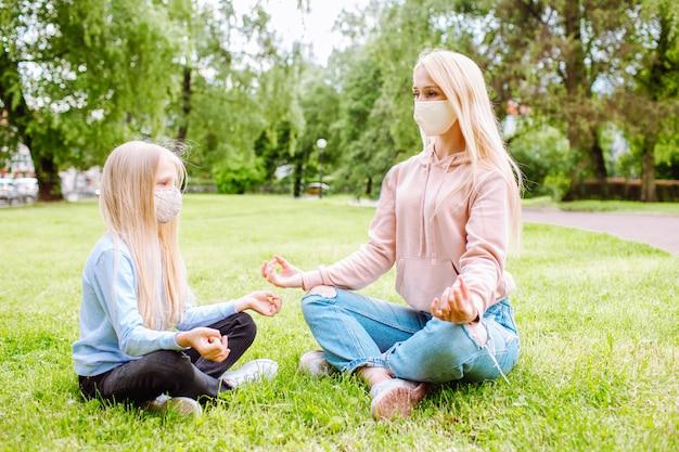 Мама и маленькая дочь в парке в защитных масках. Premium Фотографии