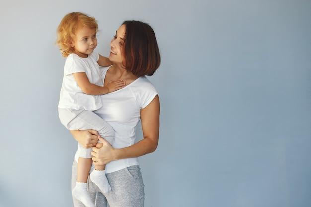 Мама и маленькая дочь развлекаются на синем фоне Бесплатные Фотографии