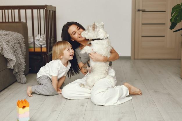 Мама и маленький сын весело дома с собакой Бесплатные Фотографии
