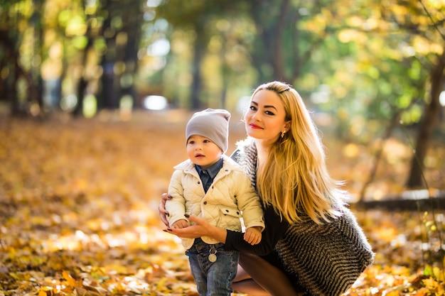 Мать и маленький сын в парке или лесу, на открытом воздухе. обниматься и веселиться вместе в осеннем парке Бесплатные Фотографии
