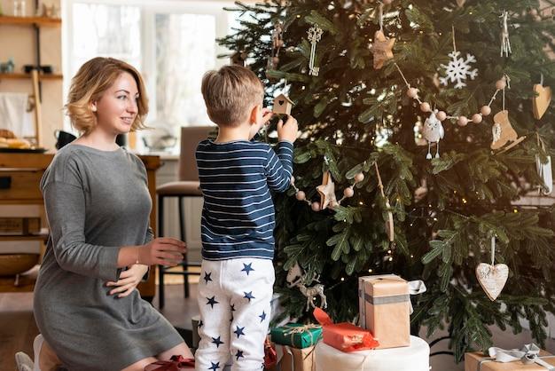 Мать и сын вместе украшают дерево Бесплатные Фотографии