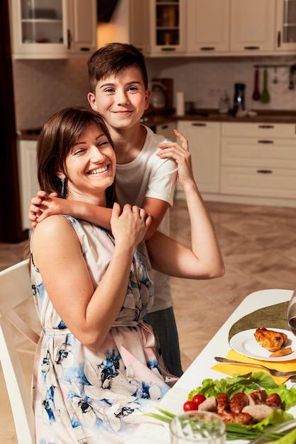 Мать и сын обнимаются за обеденным столом Бесплатные Фотографии