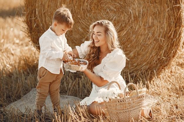 Мать и сын. стог или тюк сена на желтом пшеничном поле летом. дети веселятся вместе. Бесплатные Фотографии