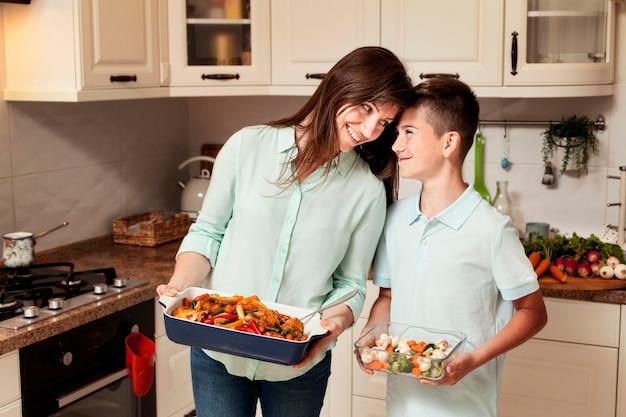 食糧を準備する台所で母と息子 Premium写真
