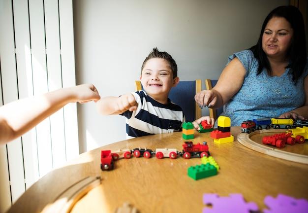 Мать и сын играют вместе за столом Premium Фотографии