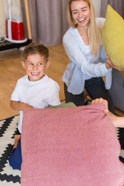 Мать и сын играют с подушками Бесплатные Фотографии