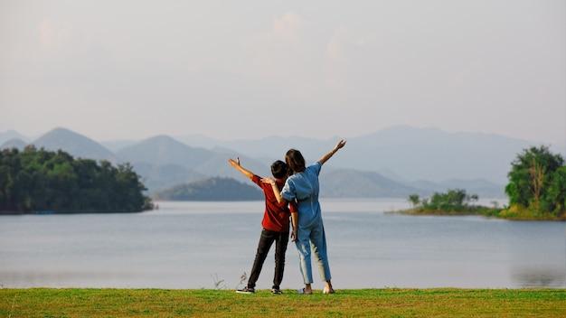 母と息子は大きな湖のそばに立って、背景に山の景色を見る。家族旅行のアイデアは、一緒に屋外旅行に旅行します。 Premium写真