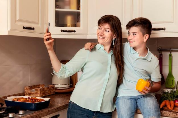 Мать и сын, принимая селфи вместе с овощами Бесплатные Фотографии
