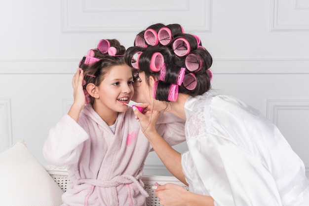 Mother applying bright lip gloss on daughters lips Free Photo
