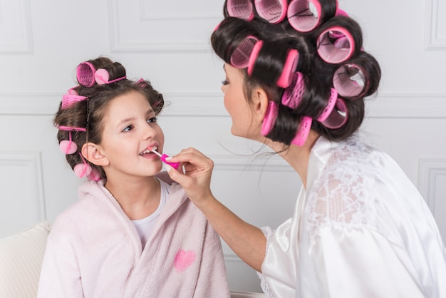 Mother applying pink lip gloss on daughters lips Free Photo