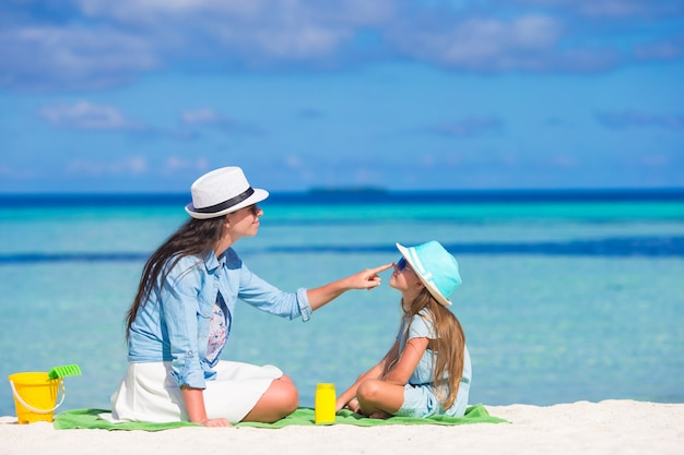Mother applying sun protection cream to her daughter at tropical beach Premium Photo
