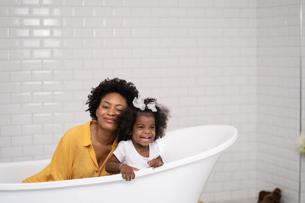 Mother and baby daughter playing together in the bathtub Premium Photo
