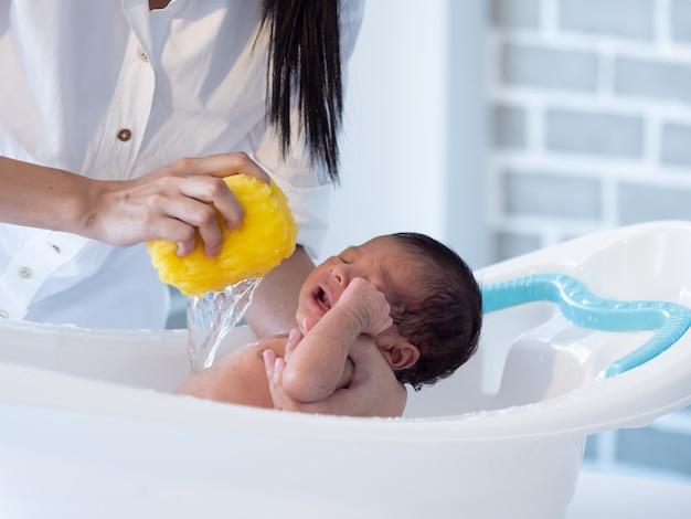 Mother bath asian boy baby newborn on the bathtub Premium Photo