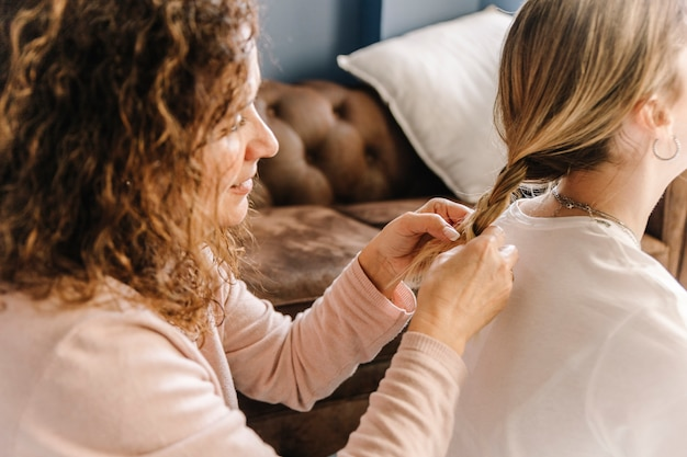 Mother braiding hair of unrecognizable daughter Free Photo