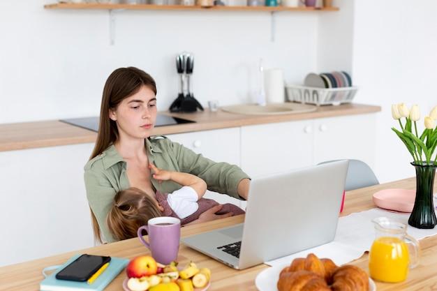 Мать кормит грудью и работает Бесплатные Фотографии