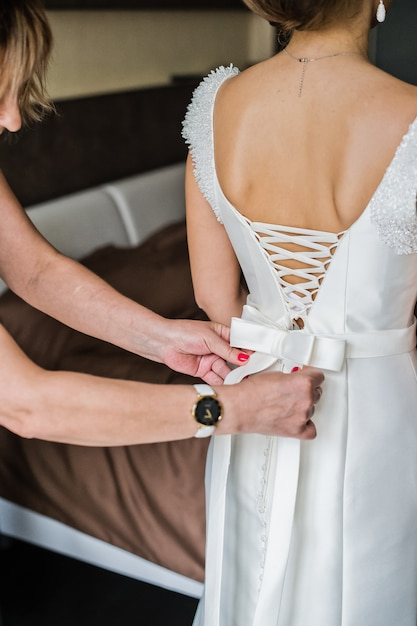 Mother of the bride helps the bride to wear a dress Premium Photo