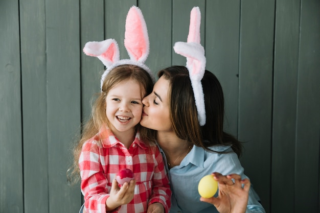 Mother in bunny ears kissing daughter on cheek Free Photo