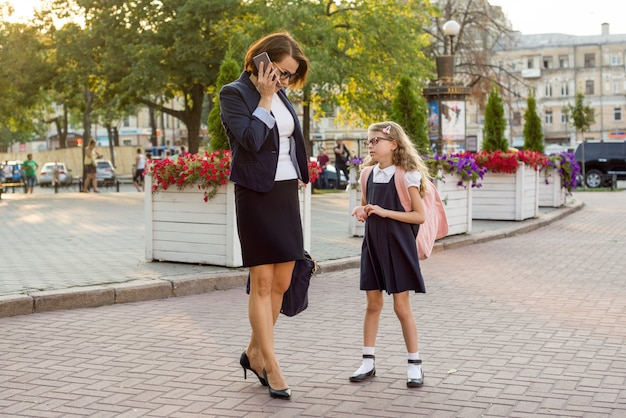 Mother businesswoman takes the child to school. Premium Photo