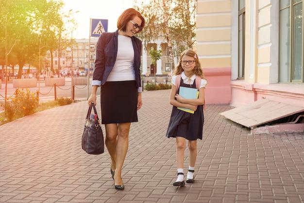 Mother businesswoman takes the child to school Premium Photo