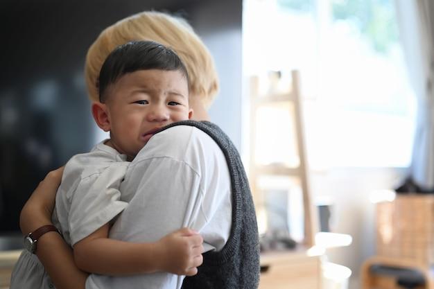 居間に立っている間、母親は泣いている赤ん坊の息子を愛撫し、落ち着かせる Premium写真