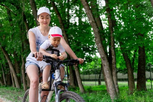 母は夏に公園の自転車で子供の椅子に子供を運ぶ Premium写真