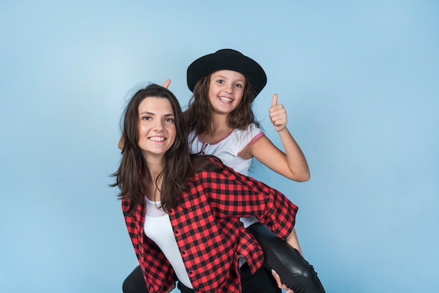 Mother carrying daughter showing thumb up on back Free Photo