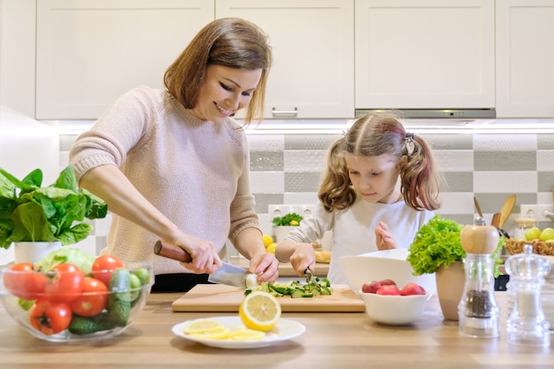 Mother and child cooking together at home in kitchen Premium Photo