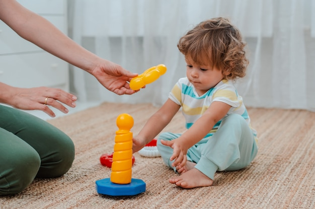Mother and child play on the floor in the nursery. mom and little baby boy are doing with plastic colorful toys. Premium Photo
