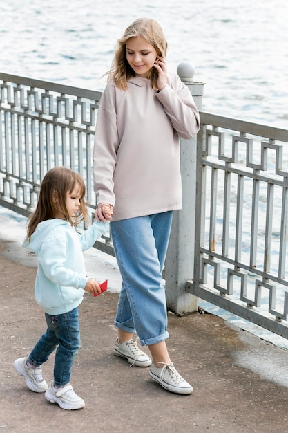 Mother and child walking by the seaside Free Photo