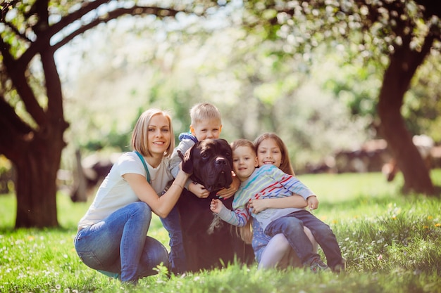 The mother, children and dog sitting on the grass Free Photo