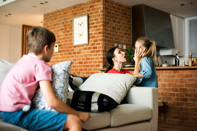 Mother consoling daughter and son sitting on the couch Premium Photo