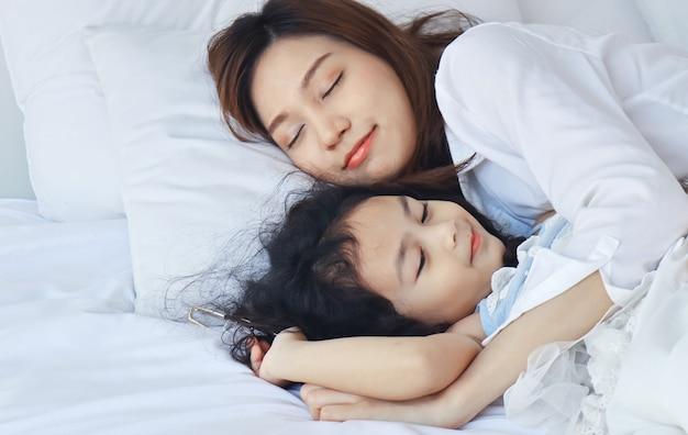 母は愛情を込めてベッドで娘を抱きしめた Premium写真