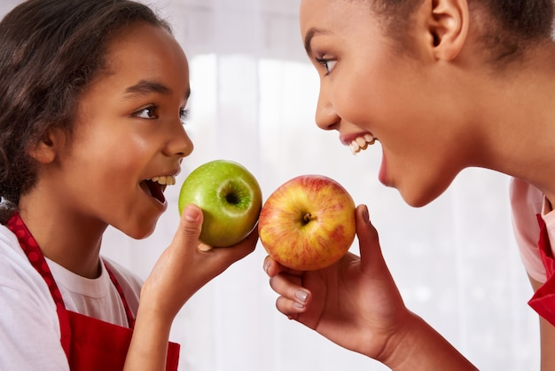 Mother and daughter in aprons eat apples in kitchen. Premium Photo