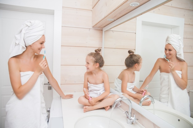 Mother and daughter are brushing teeth Premium Photo