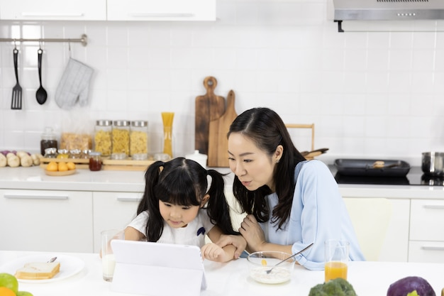 Mother and daughter are eating breakfast and watching media in a tablet Premium Photo