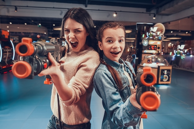 Mother and daughter are shooting guns in arcade. Premium Photo