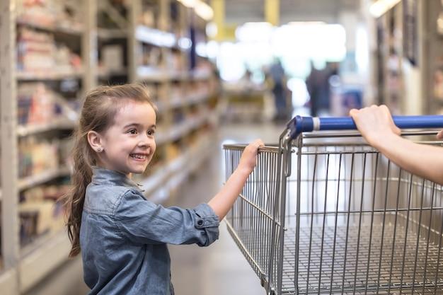 Madre e figlia in magliette blu shopping nel supermercato utilizzando il carrello Foto Gratuite