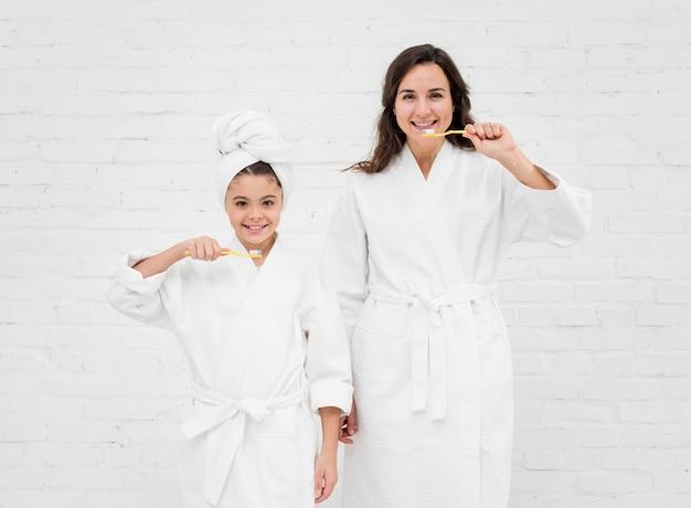 Madre e figlia lavarsi i denti Foto Gratuite