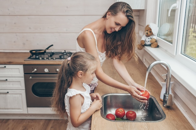 Mother and daughter cooking and washing vegetables in kitchen Premium Photo