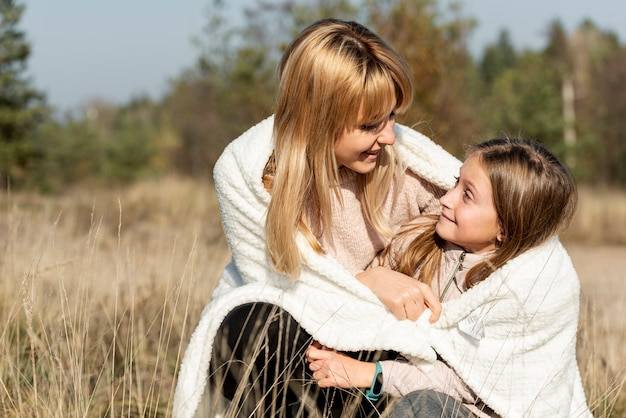 Mother and daughter covering with a blanket Free Photo