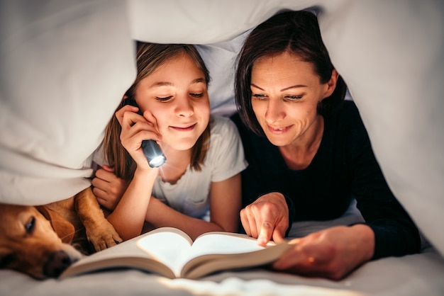 Mother, daughter and dog laying on the bed and reading book late at night Premium Photo