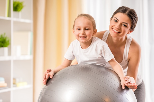 Mother and daughter doing physical exercises on fitness ball Premium Photo