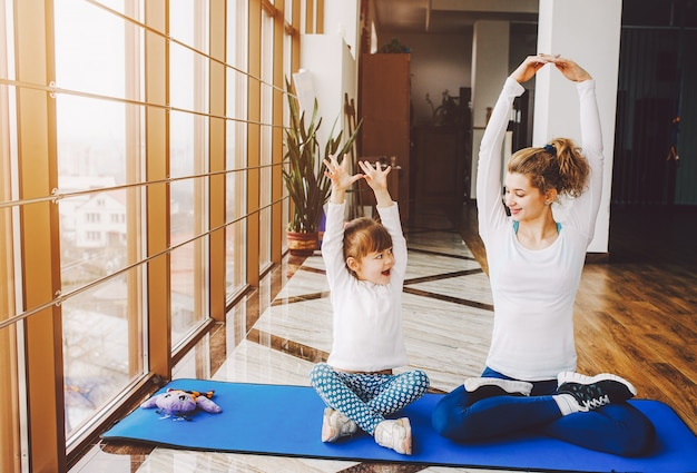 Mother and daughter doing yoga Free Photo