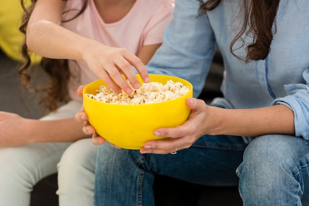 Mother and daughter eating popcorn close-up Free Photo
