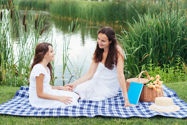 Mother and daughter enjoying picnic by the lake Free Photo